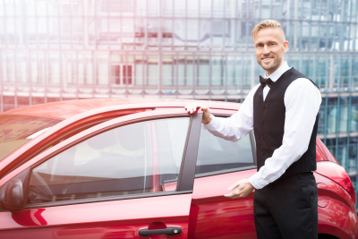 Portrait Of A handsome young man opening red car door